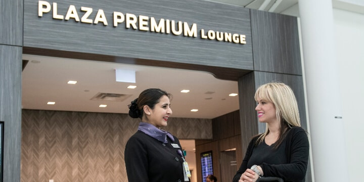 Two women standing outside the Plaza Premium Lounge entrance