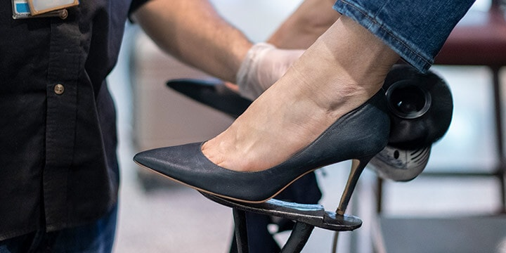 Close-up view of woman's black stiletto shoes on foot rest at Walter's Shoe Care kiosk.