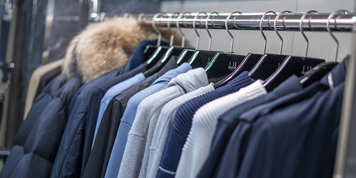 Navy, blue and grey men's shirts and jackets hanging on a rack