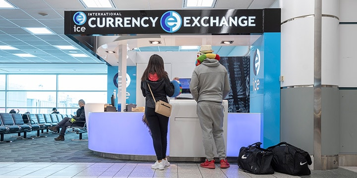 Des voyageurs au comptoir d'International Currency Exchange.